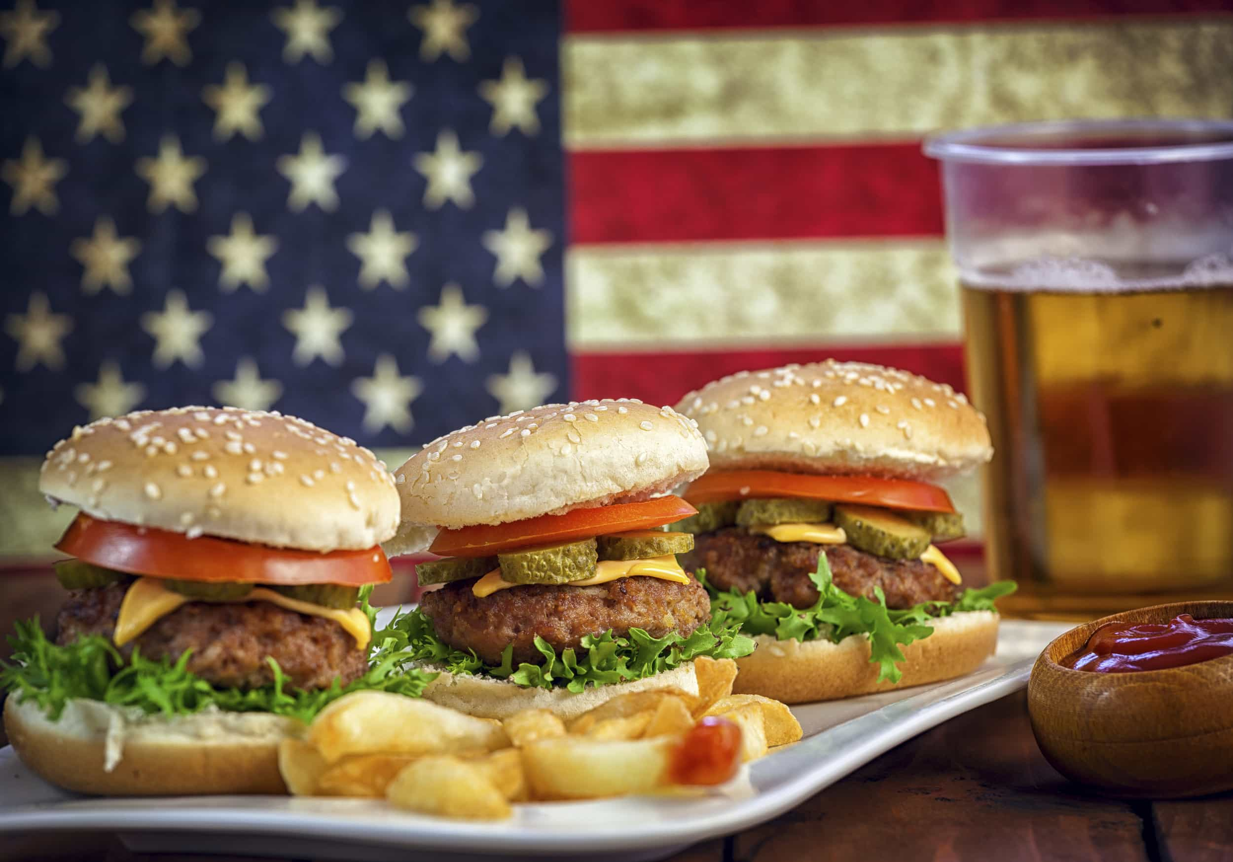 American Burger with pickles,cheese,tomato,red onion,lettuce and french fries at a Picnic for 4th of July in front of American flag